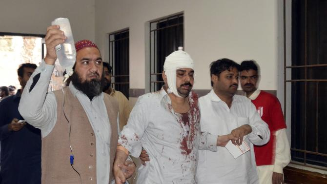 Man who was injured after an explosion in a Shi'ite mosque, walks with relatives after receiving medical treatment at a hospital in Shikarpur