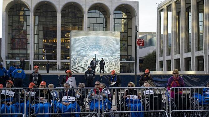 "People, some in wheelchairs, gather at Lincoln Center, with the Metropolitan Opera House in the background, as they protest ""Death of Klinghoffer"" Monday, Oct 20, 2014, in New York. American composer John Adams' opera has been a lightning rod since February, when it was first scheduled for this season. The first large demonstration came on the Met's Sept. 22 season opening night, featuring a Mozart work, when protesters jeered at arriving spectators. (AP Photo/Craig Ruttle)"