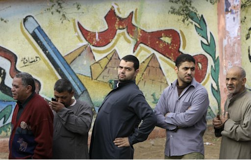 Egyptians line outside a polling station in front of a graffiti showing the Pyramids and Arabic word Egypt, in Giza, Egypt, Wednesday, Dec. 14, 2011. Egypt held Wednesday the second round of parliamentary voting, part of the first elections since President Hosni Mubarak was ousted in February. (AP Photo/Amr Nabil)