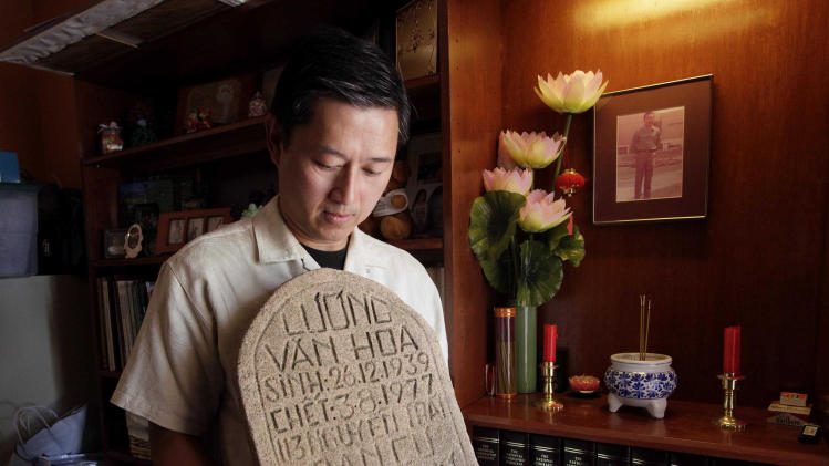 In this photo taken Friday, July 29, 2011, Daniel Luong holds the tombstone of his father, former South Vietnamese Army Capt. Luong Van Hoa, at his home in Los Angeles. Nearly a year to the day after collecting the tombstone and human remains from a grave at the former site of the Lang Da re-education camp in Vietnam in July 2010, Luong got the news that the remains were a positive DNA match for his father. He last saw his father in 1976 when he was just 12 years old. (AP Photo/Nick Ut)