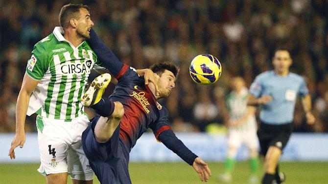 Barcelona's Leo Messi frm Argentina, right, and Betis's Antonio Amaya, left, fight for the ball during their La Liga soccer match at the Benito Villamarin stadium, in Seville, Spain on Sunday, Dec. 9, 2012. (AP Photo/Angel Fernandez)
