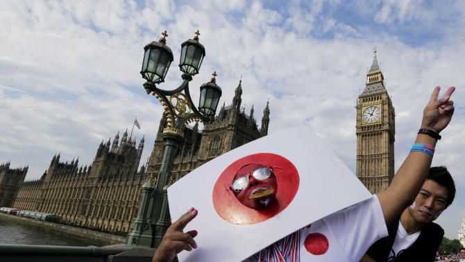 A Japanese supporter gestures near Big Ben and the Houses of Parliament, prior to the start of the men's marathon at the 2012 Summer Olympics, at the 2012 Summer Olympics, London, Sunday, Aug. 12, 2012. (AP Photo/Luca Bruno)