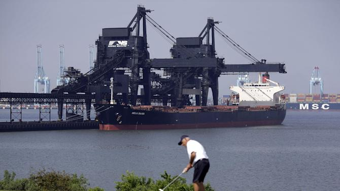In this May 22, 2014, photo, a ship is docked at Norfolk Southern's Lamberts Point coal terminal as a man plays golf in Norfolk, Va. As the Obama administration weans the U.S. off dirty fuels blamed for global warming, energy companies have been sending more of America's unwanted energy leftovers to other parts of the world, where they could create even more pollution. (AP Photo/Patrick Semansky)