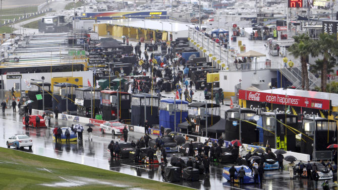 Crew members push cars into the garage after NASCAR postponed the Daytona 500 auto race in Daytona Beach, Fla., Sunday, Feb. 26, 2012, due to rain. The race has been rescheduled for Monday afternoon. (AP Photo/David Graham)