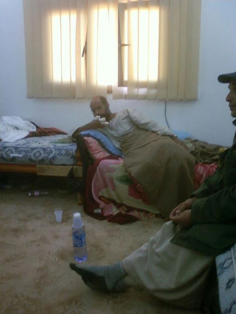Handout photograph shows Saif al-Islam, son of late former Libyan leader Gaddafi, sitting after his capture, with his fingers wrapped in bandages and his legs covered with blanket, at undisclosed location
