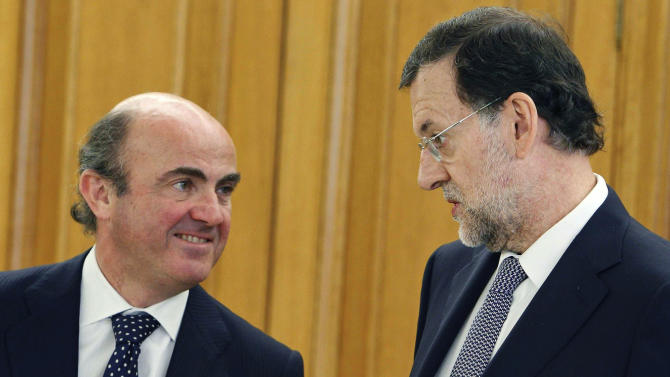 Spain's Economy Minister Luis de Guindos, left and Spain's Prime Minister Mariano Rajoy talk during a swearing in ceremony for the new governor of the Bank of Spain Luis Maria Linde, unseen, at the Zarzuela Palace in Madrid Monday June 11, 2012. The current Bank of Spain governor Miguel Fernandez Ordonez is stepping down a month earlier than scheduled. (AP Photo/Angel Diaz,Pool)