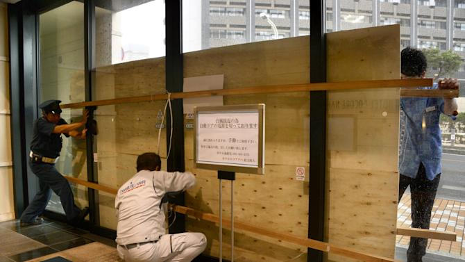 Hotel employees and a guard secure its entrance door with a plywood board in preparation for approaching typhoon Vongfong in Naha, Okinawa, Saturday, Oct. 11, 2014.(AP Photo/Kyodo News) JAPAN OUT, CREDIT MANDATORY