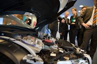Visitors look at an Audi F12 concept car during the Electric Mobility conference on May 27, 2013 in Berlin. Electric cars produce no exhaust pipe emissions and can help clear the air in congested cities