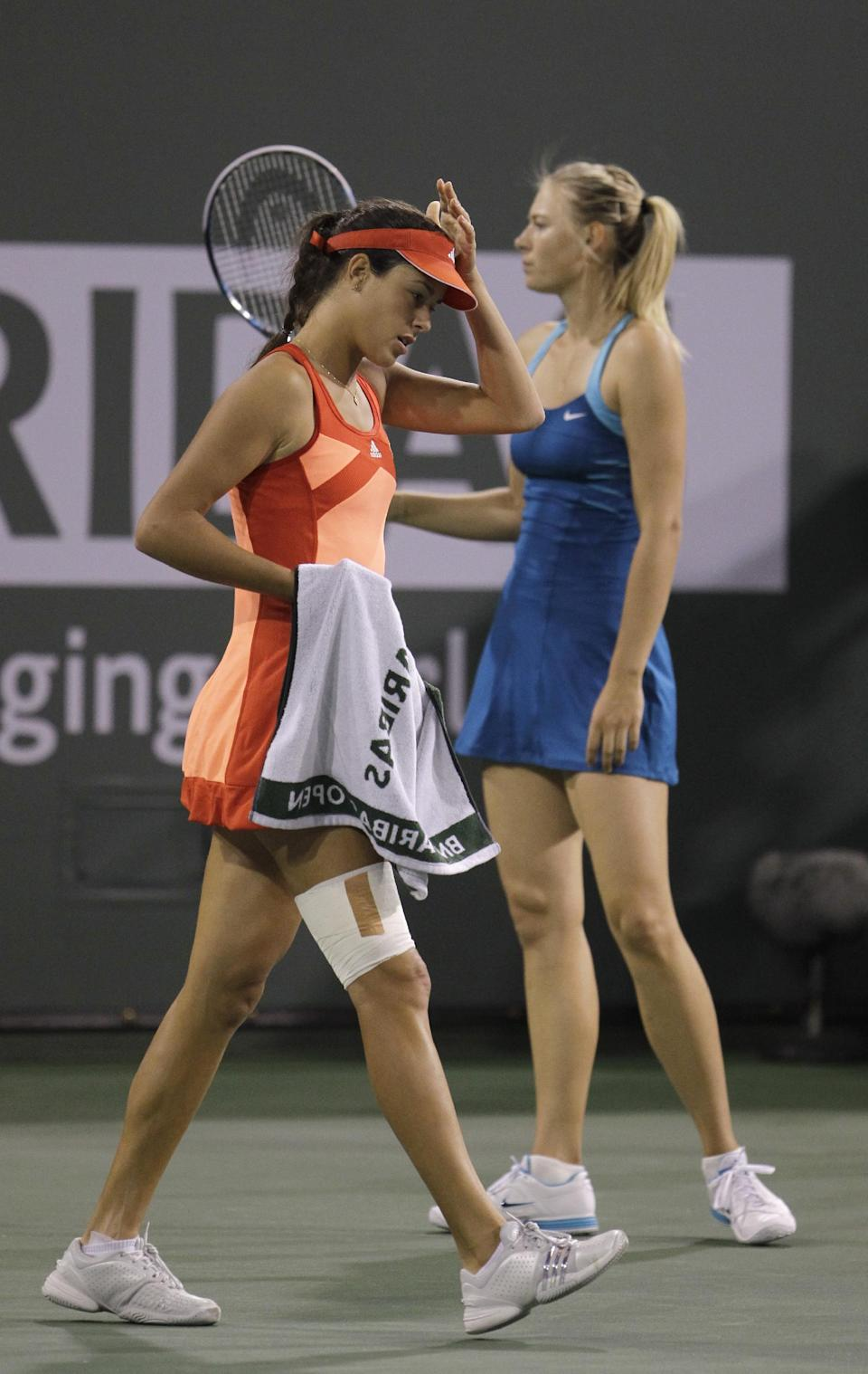 Ana Ivanovic, of Serbia, walks past Maria Sharapova, of Russia, after being treated by a trainer during a women's semifinal match at the BNP Paribas Open tennis tournament Friday, March 16, 2012, in Indian Wells, Calif. Ivanovic retired from the match due to a left hip injury. (AP Photo/Darron Cummings)