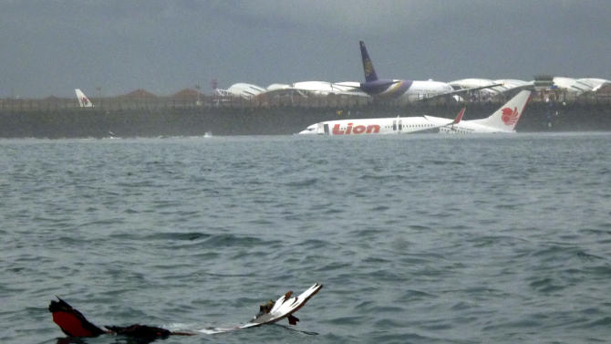 The wreckage a crashed Lion Air plane sits on the water near the airport in Bali, Indonesia on Saturday, April 13, 2013. The plane carrying more than 100 passengers and crew overshot a runway on the Indonesian resort island of Bali on Saturday and crashed into the sea, injuring nearly two dozen people, officials said. (AP Photo)
