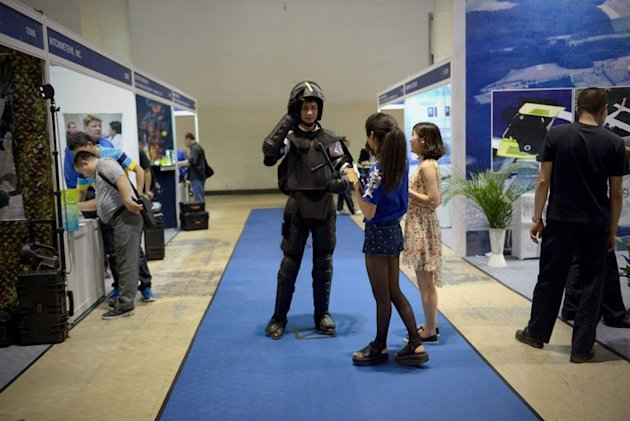 A salesman wears a suit of armour at a police equipment fair in Beijing on May 15, 2013
