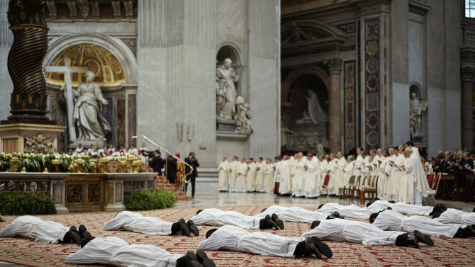 Thirteen new priests lay on the ground during a ceremony in which Pope Francis ordained them, in St. Peter's Basilica at the Vatican, Sunday, May 11, 2014. (AP Photo/Andrew Medichini)