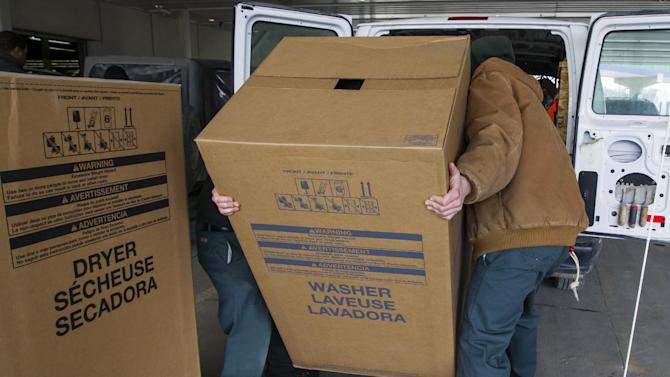In this, Wednesday, Feb. 27, 2013, photo, employees load a washer and dryer into customer's car at the loading docks of Nebraska Furniture Mart in Omaha, Neb. The Commerce Department reports on business orders for durable goods in March on Wednesday, April 24, 2013. (AP Photo/Nati Harnik)