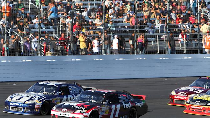 Denny Hamlin (11) competes with Jimmie Johnson during the final restart in the NASCAR Sprint Cup Series auto race at New Hampshire Motor Speedway, Sunday, Sept. 23, 2012, in Loudon, N.H. Hamlin won the race, and Johnson finished second.(AP Photo/Jim Cole)