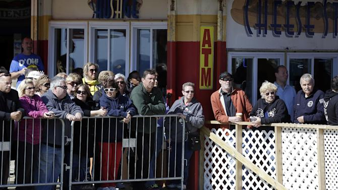 People stand behind a barricade while they wait to catch a glimpse of Britain's Prince Harry, who is expected to visit Casino Pier during a tour of the area hit by Superstorm Sandy, Tuesday, May 14, 2013, in Seaside Heights, N.J. The prince toured the community's rebuilt boardwalk, which is about two-thirds complete. New Jersey sustained about $37 billion worth of damage from the storm. (AP Photo/Julio Cortez)