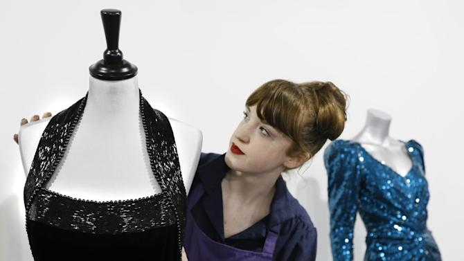The beaded neckline of a Catherine Walker black velvet evening gown worn for a Vanity Fair photo shoot by Britain's Princess Diana is adjusted by house assistant Lucy Bishop at the Kerry Taylor auction rooms in London, Thursday, Feb. 28, 2013. The dress estimated to realise 50,000-70,000 pounds ( 77,000-108,000 US Dollars) will be sold in the Fit For a Princess auction in London on March 19. (AP Photo/Kirsty Wigglesworth)