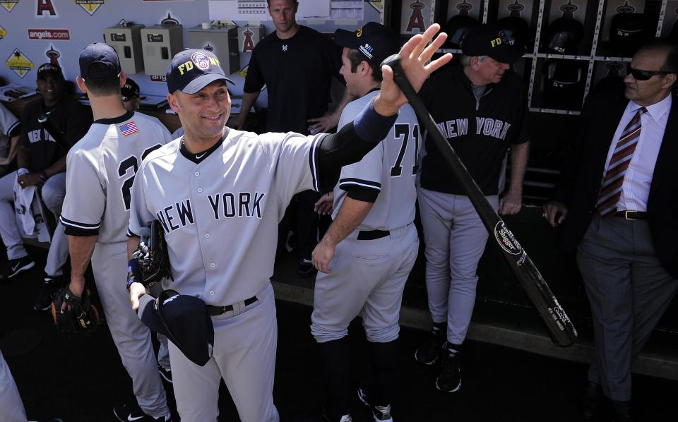 New York Yankees shortstop Derek Jeter waves as he walks into the dugout prior to a ceremony to commemorate the 9/11 anniversary prior to the Yankees baseball game against the Los Angeles Angels, Sunday, Sept. 11, 2011, in Anaheim, Calif.  (AP Photo/Mark J. Terrill)