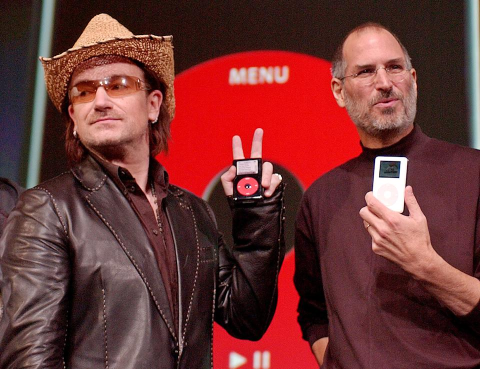 FILE - This is Tuesday, Oct. 2, 2004 file photo of  Bono, left, of the band U-2, and Apple Computers Inc. Chief Executive Steve Jobs,  hold up Apple iPods at an unveiling of a new branded iPod in San Jose, Calif.    (AP Photo/Paul Sakuma, File)