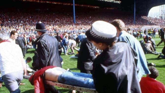 FILE - In this April 15, 1989 file photo, showing police, stewards and supporters as they tend to wounded soccer supporters on the field at Hillsborough Stadium, in Sheffield, England. 96 Liverpool fans were crushed to death in the incident at FA Cup semi-final match Liverpool against Nottingham Forest. After a long campaign by relatives of the 96 soccer fans who were crushed to death in Britain's worst sporting disaster, some 400,000 pages of previously undisclosed papers will be released Wednesday Sept. 12, 2012, and the previously secret documents may clarify what caused the disaster and how mistakes by British authorities may have contributed to the 1989 tragedy. (AP Photo, File)