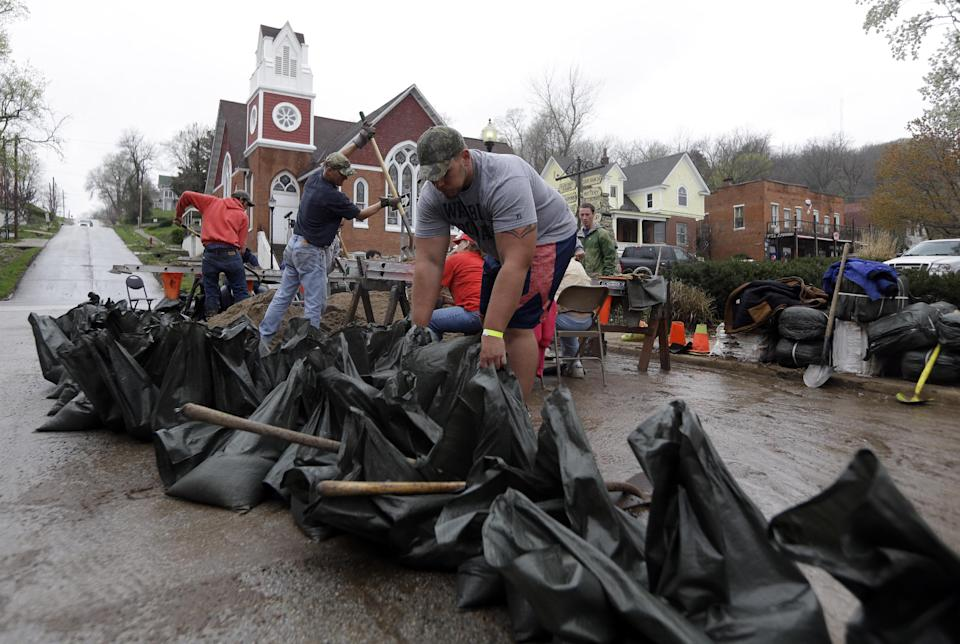 Steve Dieckhaus arranges sand bags being filled in hopes of holding back the rising Mississippi River Thursday, April 18, 2013, in Clarksville, Mo. Middle America was overwhelmed by weather Thursday, with snow in the north, tornadoes in the Plains, and torrential rains that caused floods and transportation woes (AP Photo/Jeff Roberson)
