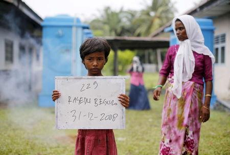 A Rohingya migrant mother (R), who recently arrived in Indonesia by boat, stands nearby as her child holds a placard while posing for photographs for immigration identification purposes inside a temporary compound for refugees in Aceh Timur regency