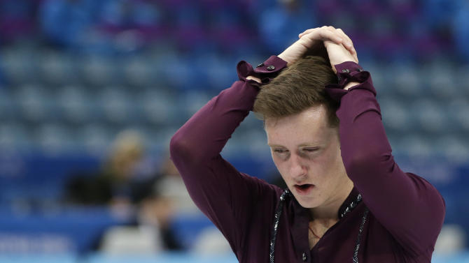 Jeremy Abbott of the United States holds his head as he skates off the ice following the men's team short program figure skating competition at the Iceberg Skating Palace during the 2014 Winter Olympics, Thursday, Feb. 6, 2014, in Sochi, Russia. (AP Photo/Darron Cummings, Pool)