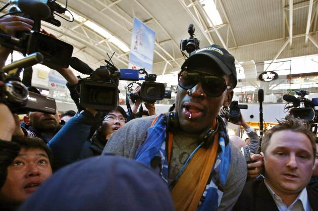 Former NBA basketball player Dennis Rodman is surrounded by media at Beijing International Airport before leaving for Pyongyang