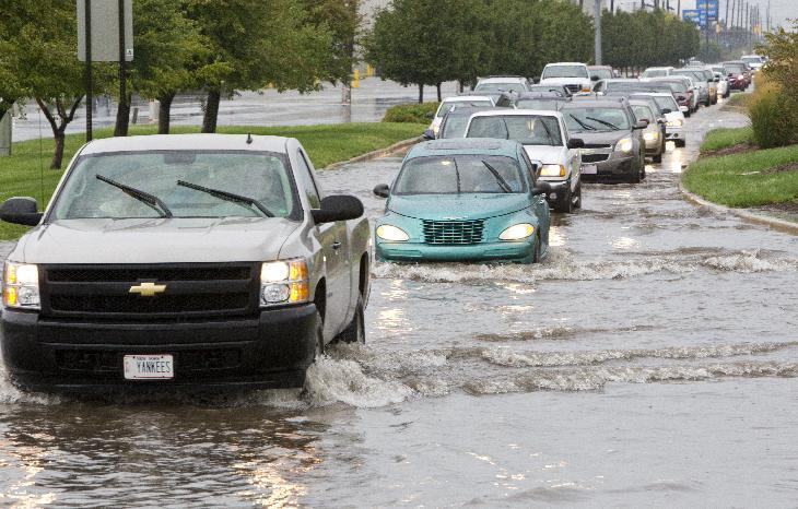 Traffic makes their way through a flooded portion of U.S. 52 after heavy rains from the remnants of Hurricane Isaac came through the area Saturday, September 1, 2012, in Lafayette, Ind. (AP Photo/Journal & Courier, Michael Heinz) MANDATORY CREDIT;  NO SALES