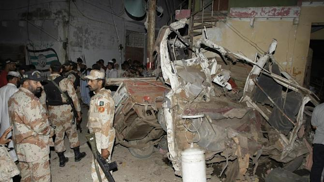 Pakistani para-military troops cordon off the site of an explosion in Karachi, Pakistan Friday, April 26, 2013.  A bomb planted near the office of a political party threatened by the Taliban has killed many people in southern Pakistan, police said. (AP Photo/Fareed Khan)