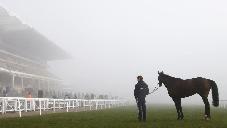 A stable boy takes The Hollinwell for a walk at the course on a foggy morning before the final day at the Cheltenham Festival horse racing meet in Gloucestershire
