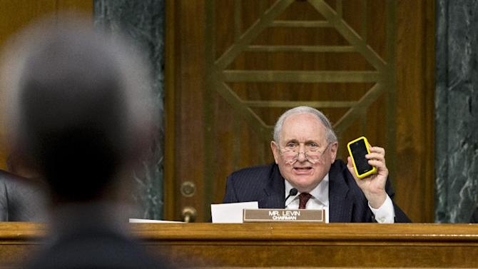 Senate Homeland Security and Governmental Affairs Permanent subcommittee on Investigations Chairman Sen. Carl Levin, D-Mich., holds up his own Apple iPhone, on Capitol Hill in Washington, Tuesday, May 21, 2013, as he presses Apple CEO Tim Cook, left, for answers about how Apple, the world's most valuable company, and based in Cupertino, Calif., diverts a billion dollars to an Irish subsidiary as a tax strategy, according to a report issued this week by the subcommittee.  (AP Photo/J. Scott Applewhite)