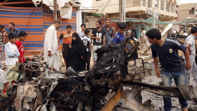 Civilians inspect the scene of a car bomb attack in the Kamaliyah neighborhood, a predominantly Shiite area of eastern Baghdad, Iraq, Monday, May 20, 2013. A wave of car bombings across Baghdad's Shiite neighborhoods and in the southern city of Basra killed and wounded scores of people, police said. (AP Photo/ Hadi Mizban)