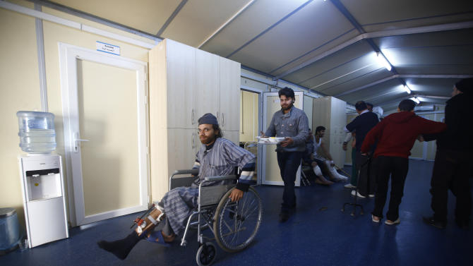 An injured Syrian man sits in a wheelchair at a small clinic near the Turkish-Syrian border in the southeastern city of Kilis