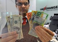 A money changer displays a selection of US dollars (L) and Australian dollar notes in Sydney, on May 14, 2012. The Australian dollar slipped below parity with the greenback on Monday and analysts tipped it could fall further as speculation mounts that the US could wind back its quantitative easing policy