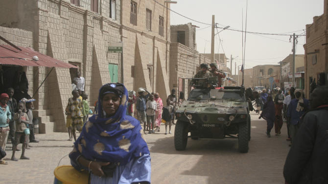 French soldiers are watched by local people, as they drive through the city streets in Timbuktu, Mali, Thursday Jan. 31, 2013.  Many things have changed in Timbuktu since the Islamic militants ceased to enforce their law and relinquished power to French special forces who parachuted in several days ago, liberating this storied city, and now there is a growing sense of freedom. (AP Photo/Harouna Traore)
