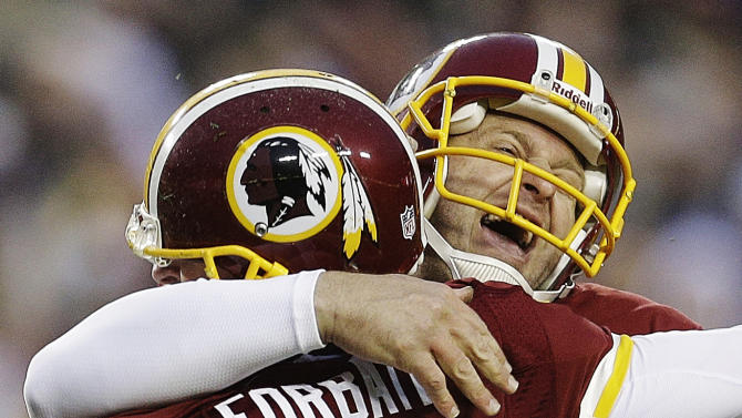 Washington Redskins' Sav Rocca, right, hugs Kai Forbath (2) after Forbath's winning 34-yard field goal in overtime of an NFL football game against the Baltimore Ravens in Landover, Md., Sunday, Dec. 9, 2012. The Redskins won 31-28. (AP Photo/Patrick Semansky)