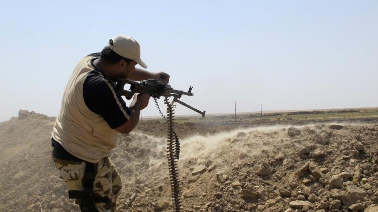 An Iraqi Shi'ite militia fighter takes his position during a patrol at the outskirts of Amerli