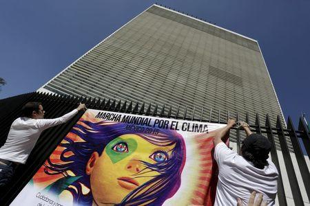Protesters place a banner on a fence in the perimeter of the Senate building as they take part in a rally held the day before the start of the 2015 Paris Climate Change Conference (COP21), in Mexico City