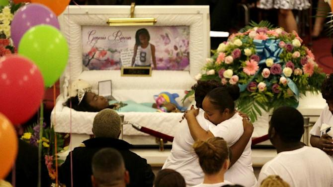 Jenny Calderon, center right, is hugged during a viewing service for her daughter, Genesis Rincon, 12, who was hit by a stray bullet while riding a scooter, in Paterson, N.J. on Friday, July 11, 2014. An assistant Passaic County prosecutor said Genesis was struck in the head around Saturday evening as she rode home to a family gathering. She was kept on life support until Monday when her organs were donated. (AP Photo/Julio Cortez)