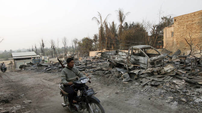 A Myanmar police officer rides a motorbike past debris of buildings and a truck destroyed during ethnic unrest between Buddhists and Muslim, as he provides security in Meikhtila, about 550 kilometers (340 miles) north of Yangon, Myanmar, Monday, March 25, 2013. Sectarian clashes between Buddhists and Muslims in Myanmar spread to at least two other towns in the country's heartland over the weekend, undermining government efforts to quash an eruption of violence that has killed dozens of people and displaced 10,000 more. On Sunday, Vijay Nambiar, the U.N. secretary-general's special adviser on Myanmar, toured Meikhtila, where soldiers were able to impose order after several days of anarchy, and called on the government to punish those responsible. (AP Photo/Khin Maung Win)