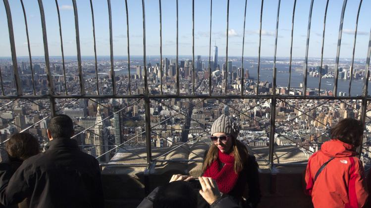 A tourists poses for photo with One World Trade Center in background from observation deck of Empire State Building in New York