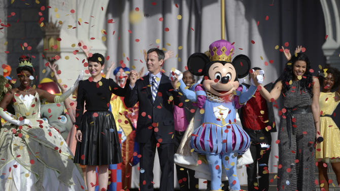 An actor dressed as the character Tiana, from left, actress Ginnifer Goodwin, Walt Disney World Parks and Resorts Chairman Tom Staggs, the character Mickey Mouse, and singer Jordin Sparks stand onstage for the grand opening celebration of the New Fantasyland attraction at the Walt Disney World Resort's Magic Kingdom theme park in Lake Buena Vista, Fla., Thursday, Dec. 6, 2012. The new attraction is the largest expansion at the Magic Kingdom.(AP Photo/Phelan M. Ebenhack)