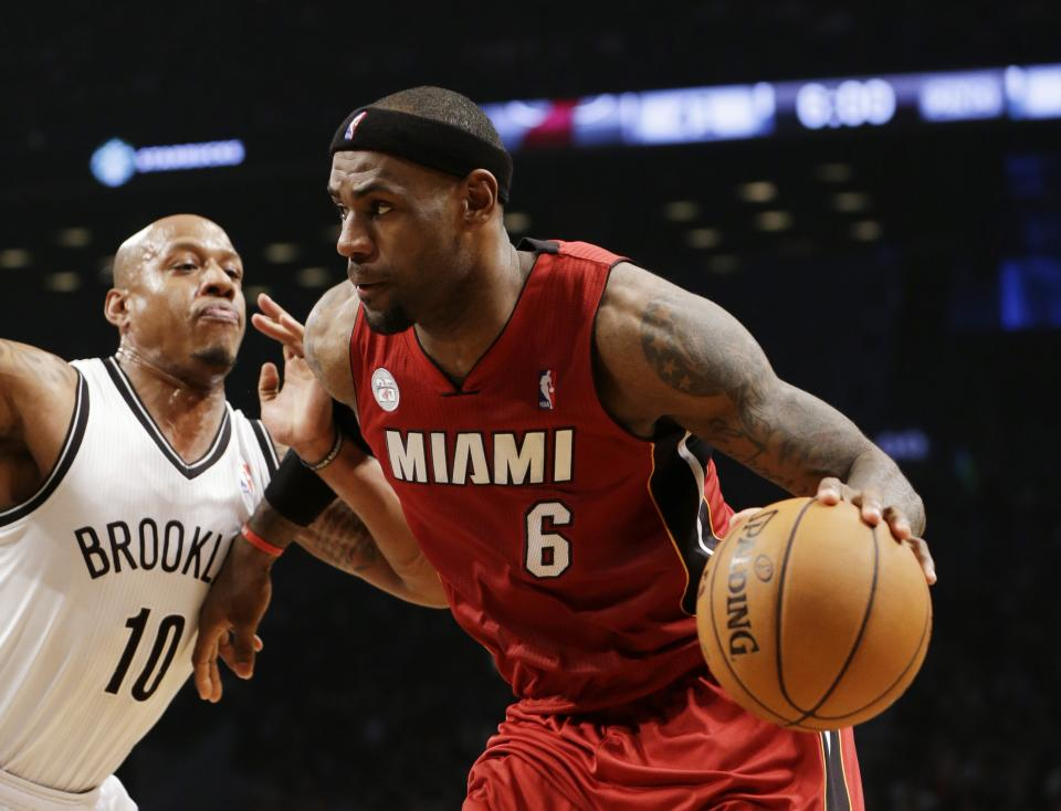 Brooklyn Nets forward Keith Bogans (10) defends as Miami Heat forward LeBron James (6)  drives toward the basket in the first half of an NBA basketball game, Wednesday, Jan. 30, 2013, in New York. The Heat won 105-85. (AP Photo/Kathy Willens)