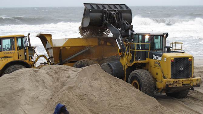 As a reporter from The Weather Channel gets set to do a broadcast on the nor'easter hitting Point Pleasant Beach N.J. , Wednesday, Nov. 7, 2012, as workers use heavy equipment to hurriedly push piles of sand back onto the beach that was damaged last week by Superstorm Sandy. Renewed flooding and power outages were expected with the latest storm. (AP Photo/Wayne Parry)