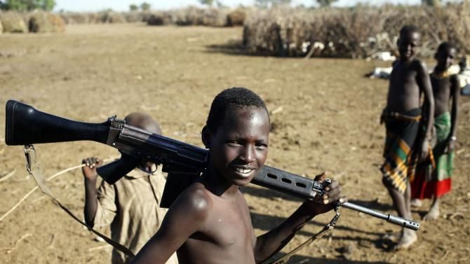 A Turkana boy plays with a rifle in a village inside the Turkana region of the Ilemi Triangle