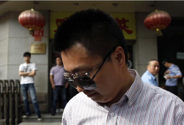 Du Yanling wears sunglasses, similar to those of blind Chinese activist Chen Guangcheng, over his normal glasses outside the hospital where Chen is recuperating in Beijing, China, Thursday, May 3, 201