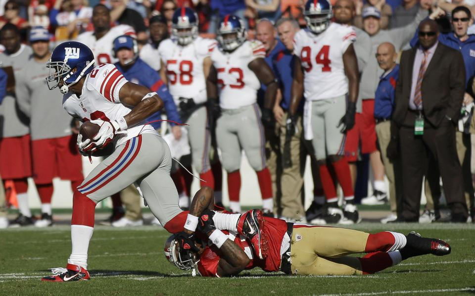 New York Giants cornerback Corey Webster (23) runs with an interception as San Francisco 49ers wide receiver Ted Ginn Jr. (19) grabs his leg in the second quarter of an NFL football game in San Francisco, Sunday, Nov. 13, 2011. (AP Photo/Marcio Jose Sanchez)