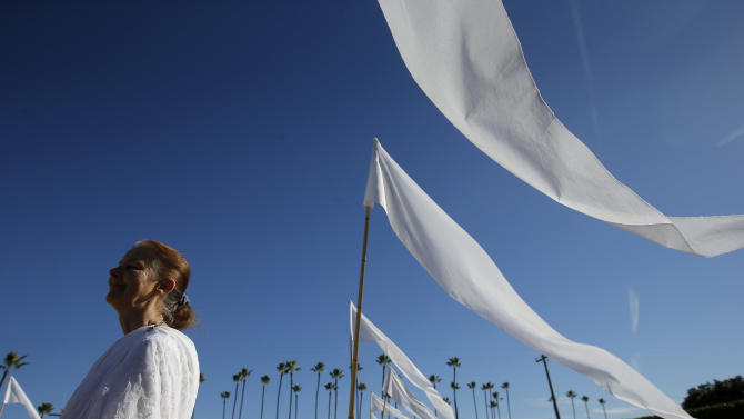 Usher Kritagyata Nicholls stands next to white flags during a memorial service for Indian Sitar maestro Ravi Shankar in Encinitas, Calif., Thursday, Dec. 20, 2012. Shankar was a master of the Indian sitar who collaborated with and influenced George Harrison, John Coltrane and other Western music icons. He lived in Encinitas for two decades and died last week at age 92. (AP Photo/Jae C. Hong)