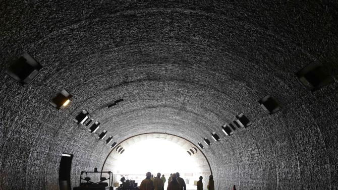 Caltrans and media members make their way out of a southern portal of the Devil's Slide tunnel project in Pacifica, Calif. Wednesday, Feb. 13, 2013. It's been almost 50 years since California built a tunnel, but this month one of the largest engineering jobs in the U.S. today is expected to open, moving motorists from a stunning, cliffhanger of a drive to straight and well lit pair of 4,200-foot tunnels carved through the stony cliffs of the California coastline. The $439 million project, paid entirely by the federal government, features exhaust fans, carbon monoxide sensors, and a pair of 1,000 foot bridges which soar 125 feet above a grassy ranch. (AP Photo/Eric Risberg)