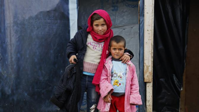 A Syrian refugee girl stands with her brother near their tent at a refugee camp in Zahle in the Bekaa valley
